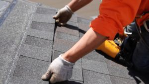 Placing new roofing shingle on a roof repair